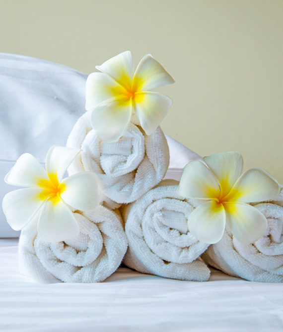 Rolled white towels with yellow and white flowers decorating them