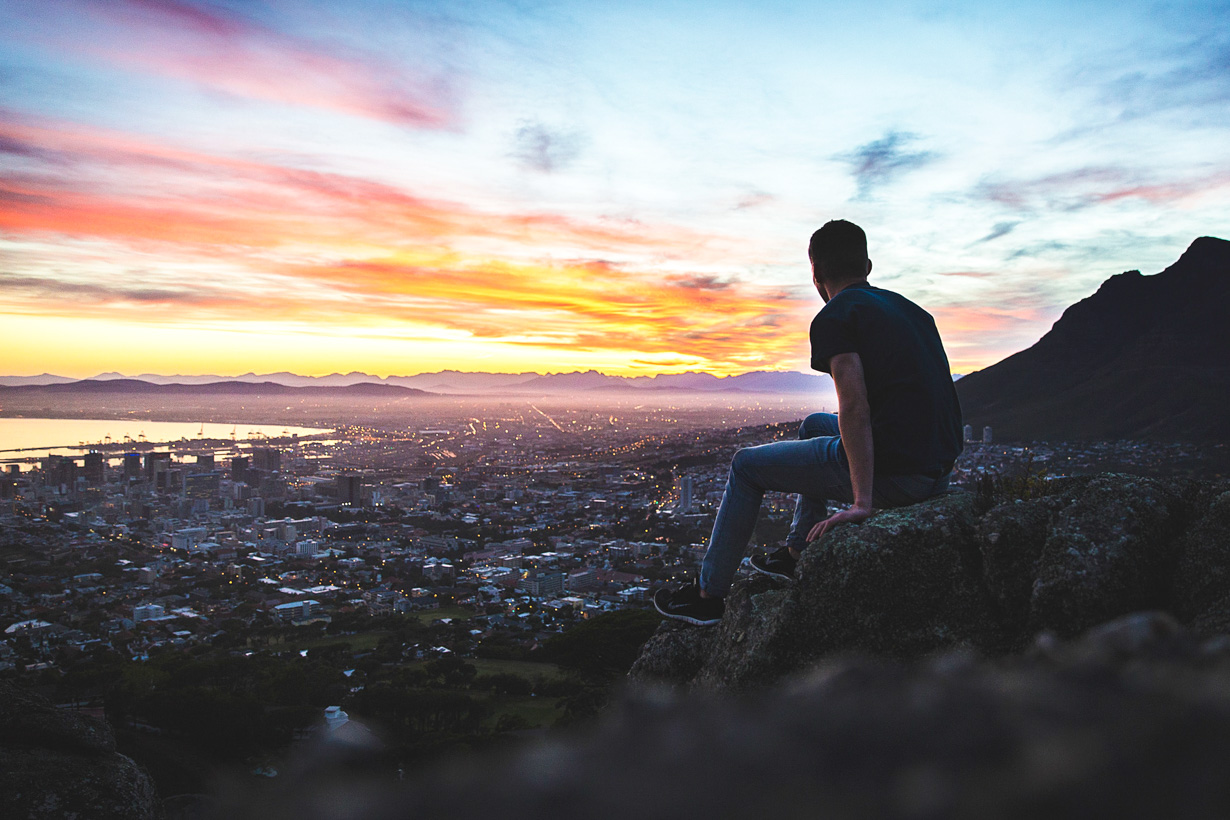 Man sits on rock to overlook Cape Town, South Africa
