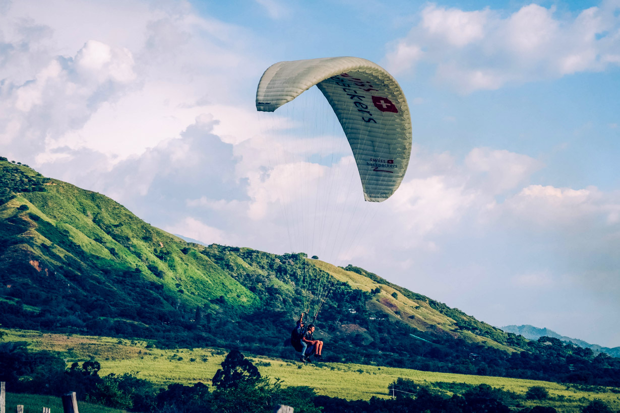 Two people paraglide near green hills in Colombia