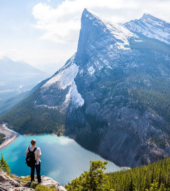 Traveler stands on overlook of mountain lake