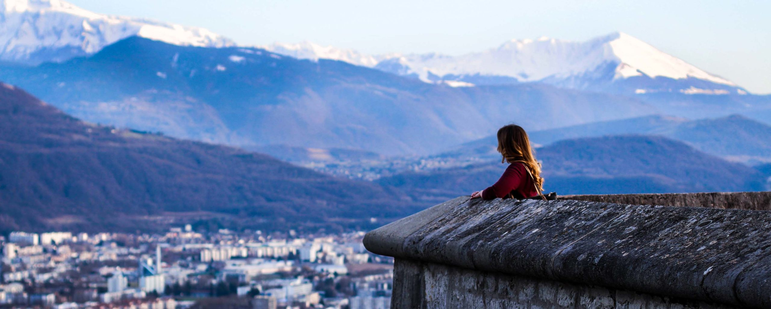 Woman overlooks city from top of building