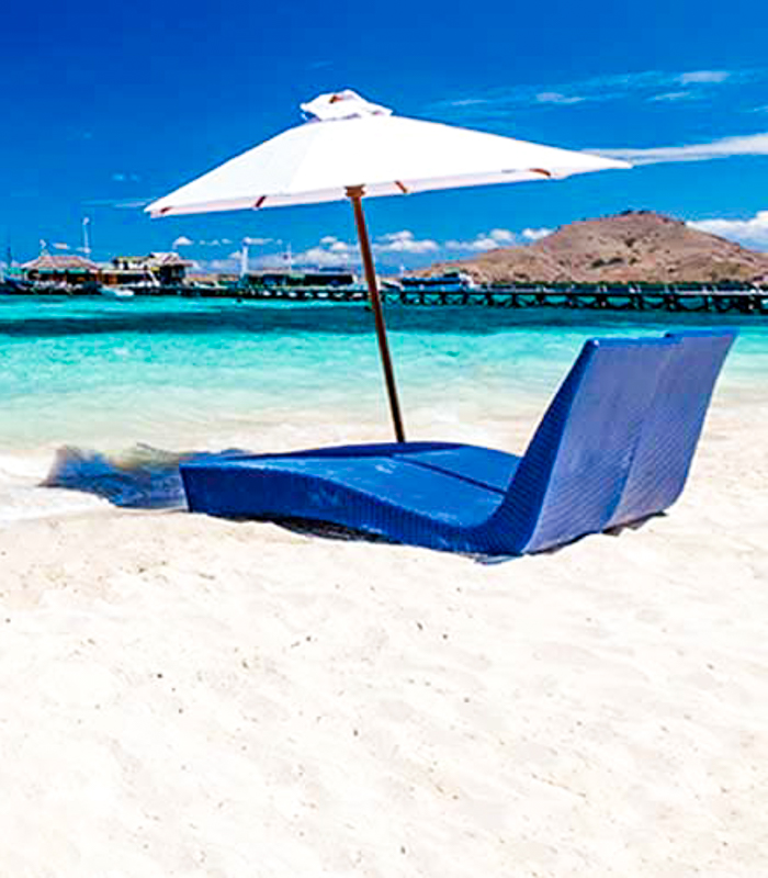 Two blue chairs and a white umbrella on white sand beach