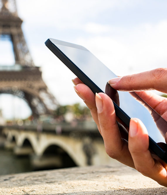 Hand holds mobile phone with Eiffel Tower in background