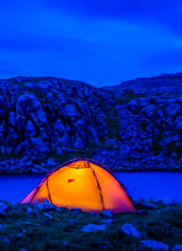 Tent glows orange against river in late evening